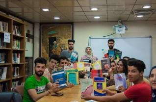 طلاب الجامعة المستنصيرية بالعراق يرفعون الكتب دعما لمبادرة العلاقات العامة للجميع